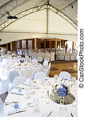 a typical wedding under a tent with tables set for eating dinner