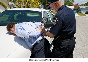 Under Arrest - Police officer handcuffing and arresting a...