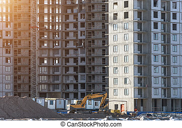 Under construction apartment building and residential real estate, excavator on the ground