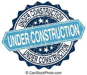 under construction blue round grunge stamp on white
