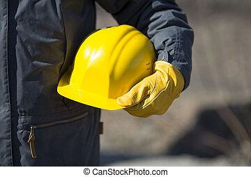 under construction concept - hand of worker with yellow hard...
