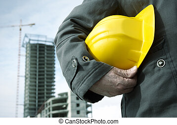 under construction - focus point on the hard-hat and hand, ...