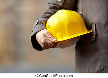 under construction - hand of builder with yellow hardhat,...