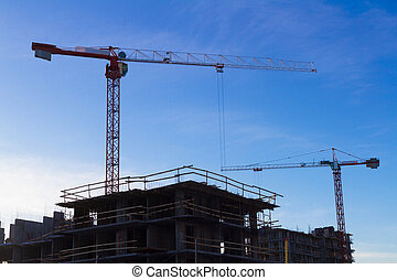 Under construction high-rise building with two cranes the background of blue sky
