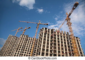 Under construction houses with cranes