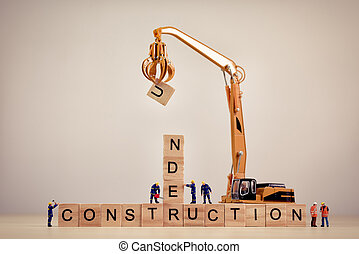 Under Construction sign on wooden tiles. Macro concept