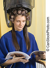 young woman sitting under a hairdryier with roller on head