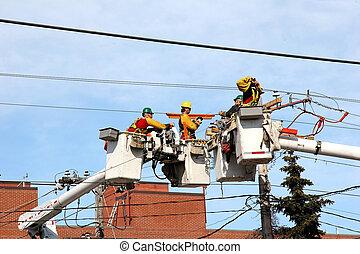 Under Repair - Electrical workers repairing power lines from...