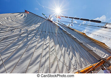 Bay City Tall Ship Celebration - Sun burst shining down along a large canvas sail under beautiful bright blue skies. Perfect sailing.