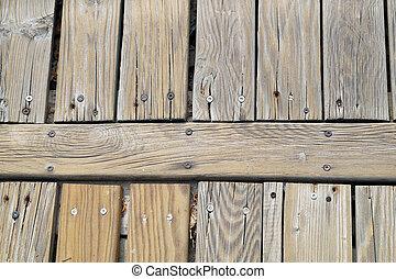 Under the blue sky , platform pier wood beside sea .