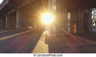 Under the concrete bridge through the spans the sunbeam shines brightly.