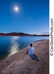 Under the Moon light Woman sitting by the lake