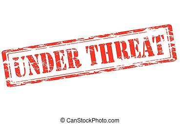 Under threat - Rubber stamp with text under threat inside,...