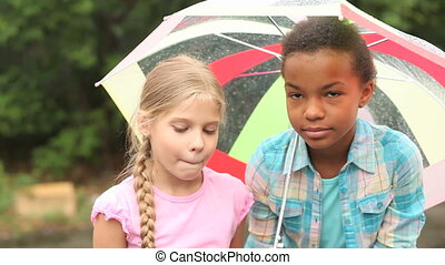 Under umbrella - Charming girls hanging out outside in the...