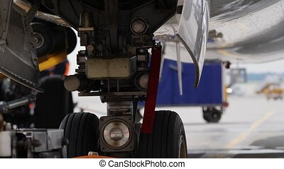 Undercarriage of parked airplane with red warning Remove before flying ribbon
