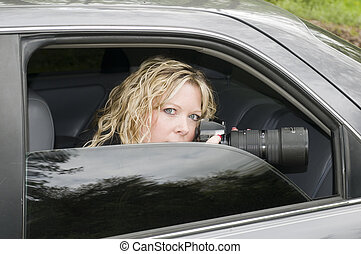 attractive secret agent undercover police woman or investigator spying with a long telephoto lens camera from a darkened window car