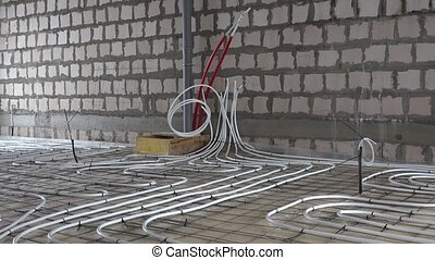 Underfloor heating system pipes tubes at construction site. ...