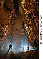 Monumental cave hall with speleologists exploring it