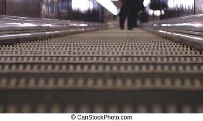 Underground escalators at rush hour. Blurred background with...