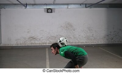 Underground parking. A young deft soccer man training...