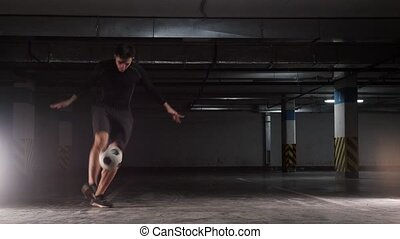 Underground parking. A young soccer man showing the basic...