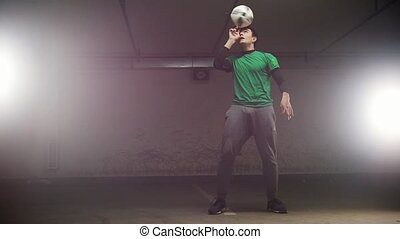 Underground parking. A young soccer man training football...