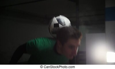 Underground parking. A young soccer man training football tricks. Throwing the ball in the air and catching it on his neck