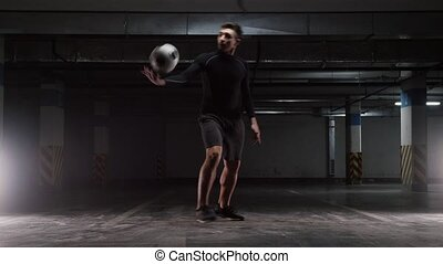 Underground parking. A young soccer man training tricks with the ball
