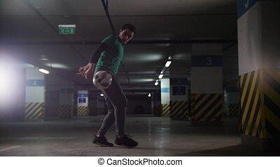 Underground parking. Athletic soccer man training his...