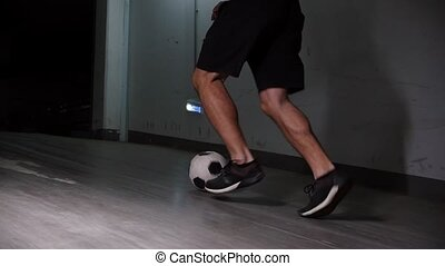 Underground parking lot. A soccer man leading the ball using...