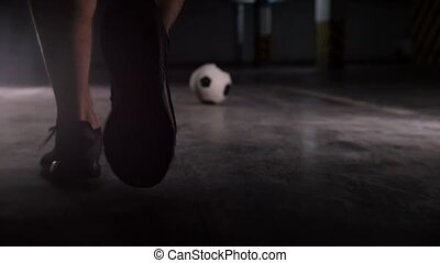 Underground parking lot. A soccer man runs to the ball and...