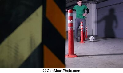 Underground parking lot. A soccer man training his football...