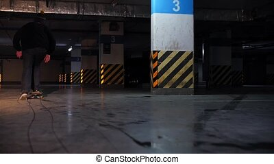 Underground parking lot. A young man practicing skateboarding. Mid shot