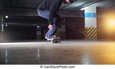Underground parking lot. A young man skateboarding. Making a spin and continue skating. Mid shot