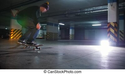 Underground parking lot. A young man skateboarding. Practicing the ollie trick