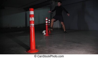 Underground parking lot. Athletic soccer man training his...