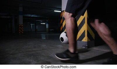 Underground parking lot. Soccer man training his football skills. Leading the ball around concrete pillar. Mid shot