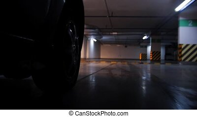 Underground parking. Moving car wheel in the frame. Overcome...