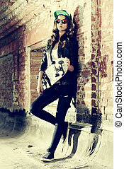 underground - Modern girl teenager stands with skateboard...