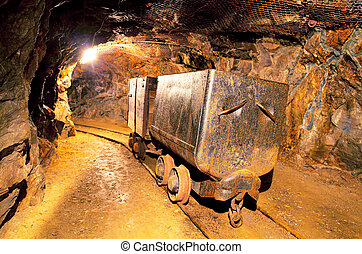 Underground train in mine, carts in gold, silver and copper...
