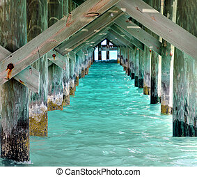 underneath ocean pier with turquoise water