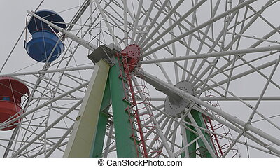 Underside view of a ferris wheel over blue sky.