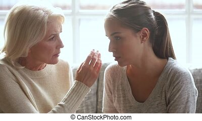 Understanding loving senior mother worried about upset young daughter having problem trust talk to caring old mom comforting consoling sad grown woman in trouble share problem with mature mum at home.