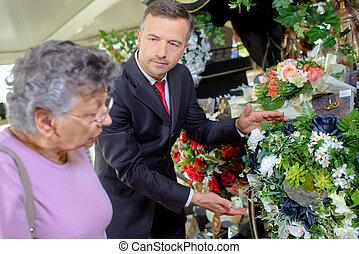 Undertaker helping woman choose flowers