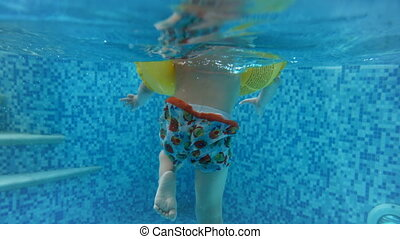 Underwater 4k video of childs' feet in inflatable ring...