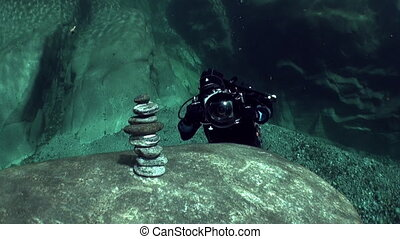 Underwater cameraman makes shot about pyramid of stones in...