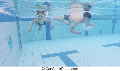 Happy little girl and boy wearing snorkel and mask having fun at summer holidays vacation enjoying recreational leisure time swimming in the pool in aquapark. Underwater footage clip of children swimming and diving in waterpark.