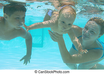 Underwater family in swimming pool. Mother teaching her kids