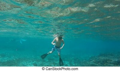 Underwater footage of a young boy snorkeling - Underwater...