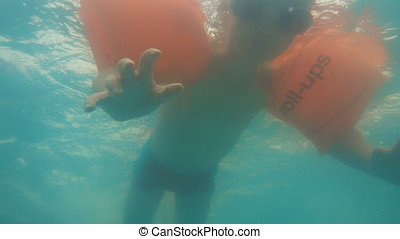 Underwater footage of little boy floating in swimming pool, slow motion